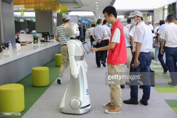 Staff member touches the screen of a 5G-supported intelligent robot at the administration service centre on August 14, 2020 in Zhoushan, Zhejiang...