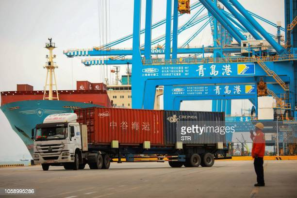 Staff member watches over a truck as he talks on his interphone at a port in Qingdao, east China's Shandong province on November 8, 2018. - China's...