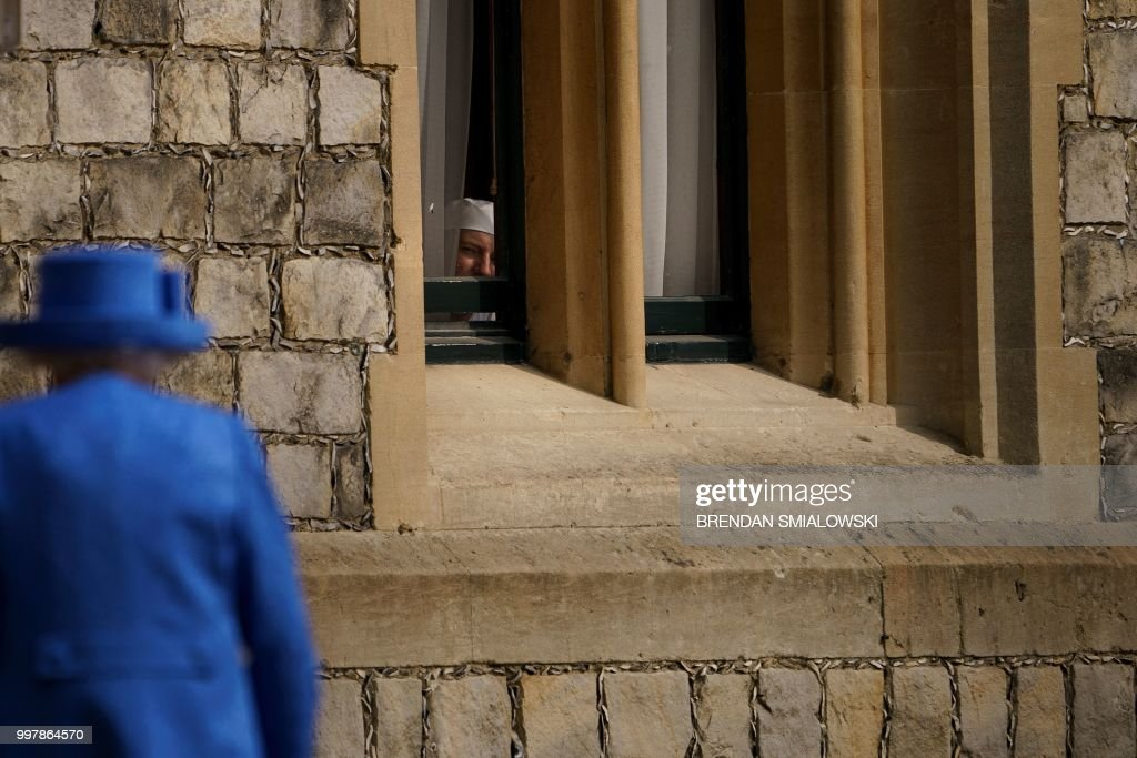 A staff member watches through a window as Britain's Queen Elizabeth II returns from inspecting the Guard of Honour with US President Donald Trump at Windsor Castle in Windsor, west of London, on July 13, 2018 on the second day of Trump's UK visit. - Queen Elizabeth II welcomed US President Donald Trump for tea at Windsor Castle on Friday -- a meeting which many Britons find the toughest part of his already contentious trip to swallow.