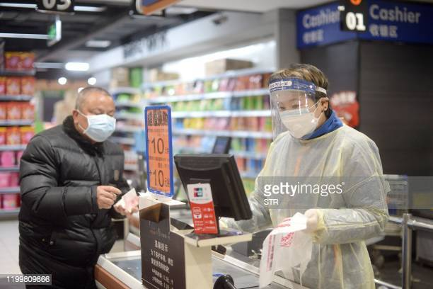 Staff member wearing a protective mask and suit works at a supermarket in Wuhan, the epicentre of the outbreak of a novel coronavirus, in China's...