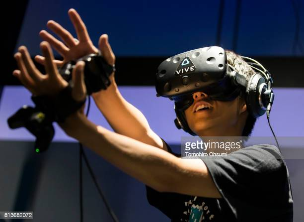 A staff member wearing an HTC Corp Vive virtual reality headset tries the Dragon Ball VR Master the Kamehameha VR attraction at the VR Zone Shinjuku...