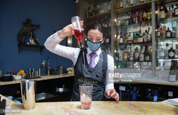 Staff member wearing protective face mask makes a cocktail at Burgh Island Hotel on July 07, 2020 in Bigbury-on-Sea, United Kingdom. The Art Deco...