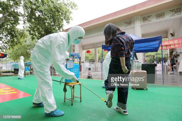 A staff member wearing protective suit disinfects the shoes of a student at Xizang Minzu University on the first day of its reopening on May 9 2020...