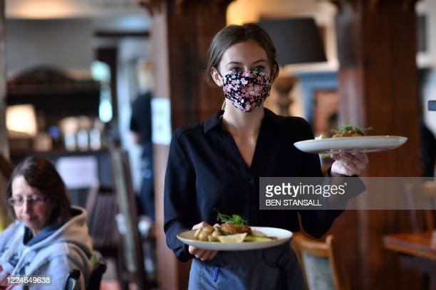 Staff member wears a face mask as she serves customers at the The Shy Horse pub and restaurant in Chessington, Greater London on July 4 on the first...