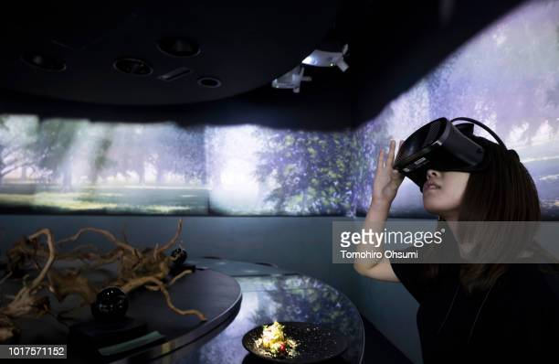 A staff member wears a virtualreality headset as the 'Spur' dish is served during a demonstration in the main dining room of the Tree by Naked Yoyogi...