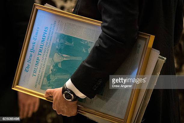 A staff member with the transition team carries a printing press plate of the November 9th edition of The New York Times at Trump Tower November 22...