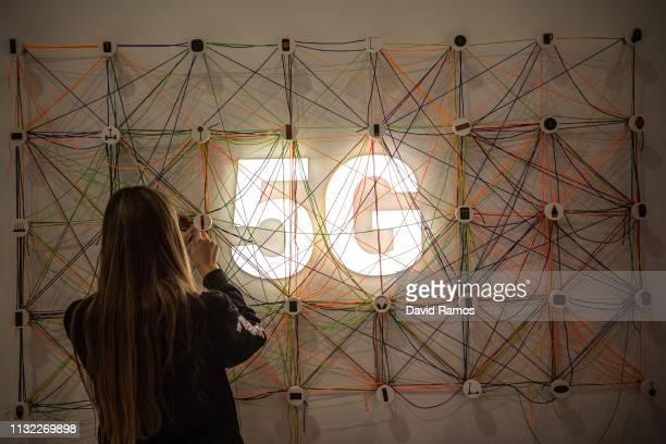 A staff member works next to a 5G logo at the Xiaomi booth on day 2 of the GSMA Mobile World Congress 2019 on February 26 2019 in Barcelona Spain The...