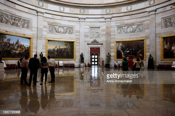 Staff members and interns admire the rotunda of the U.S. Capitol Building on August 06, 2021 in Washington, DC. The halls of Congress were quiet as...
