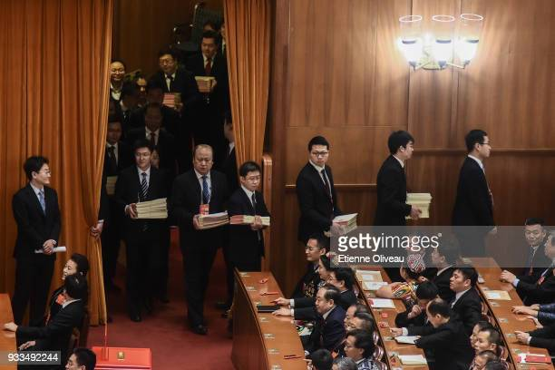 Staff members bring the ballots before the vote during the sixth plenary session of the National People's Congress at the Great Hall of the People on...