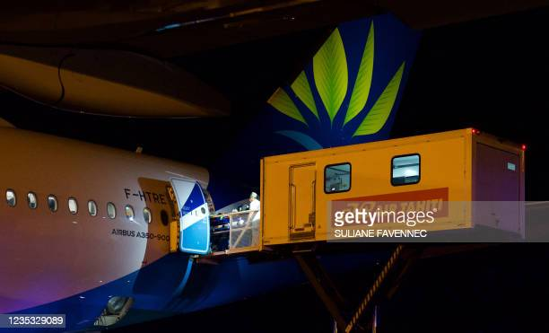 Staff members carry a patient on a stretcher into an Air Caribe Airbus A 350 airplane which has been transformed in a mobile hospital, during a...