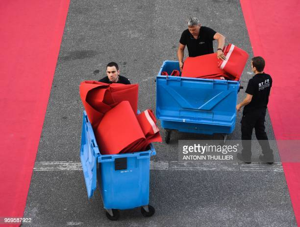 Staff members change the red carpet outside the festival's palace on May 17 2018 after the screening of the film Capharnaum at the 71st edition of...
