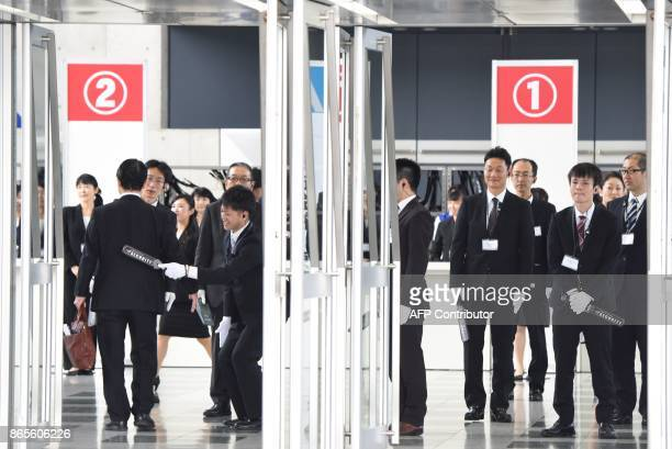 Staff members check belongings at the entrance of an extraordinary shareholders meeting of Toshiba in Chiba suburb of Tokyo on October 24 2017...