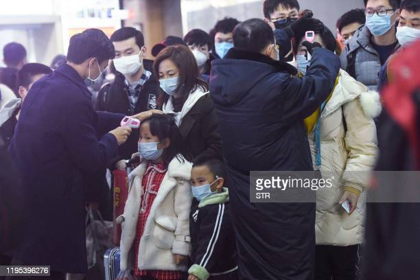 TOPSHOT Staff members check the body temperature of passengers after a train from Wuhan arrived at Hangzhou Railway Station in Hangzhou China's...