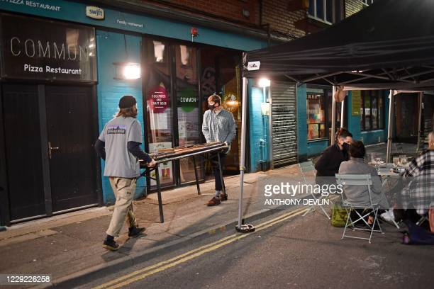 Staff members clear away the furniture from an outside bar in Manchester city centre northwest England on October 22 2020 ahead of new coronavirus...