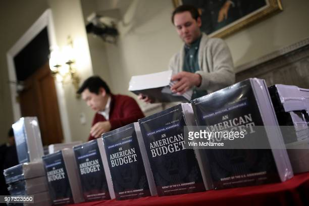 Staff members display recently released printed copies of US President Donald Trump's fiscal year 2019 budget at the House Budget Committee on...