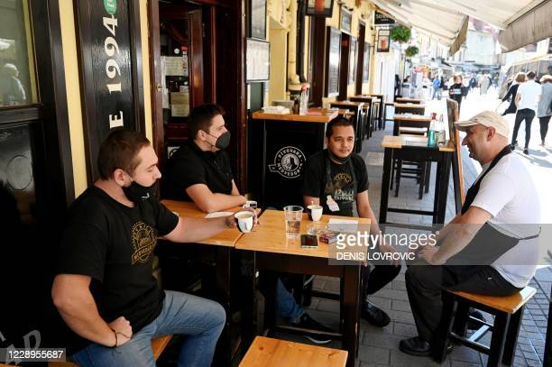 Staff members drink coffee on a deserted terrace during a protest to draw attention to the bars and restaurants difficult economic situation due to...