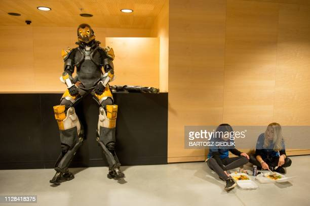 Staff members eat next to a man wearing a Fortnite character costume during the Intel Extreme Masters Katowice 2019 event in Katowice on March 2,...