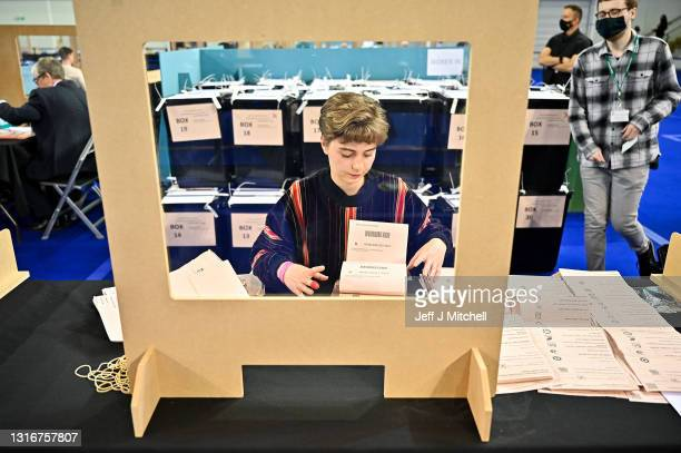 Staff members empty a ballot box at the main Glasgow counting centre in the Emirates Arena on May 06, 2021 in Glasgow, Scotland. All 129 Members of...