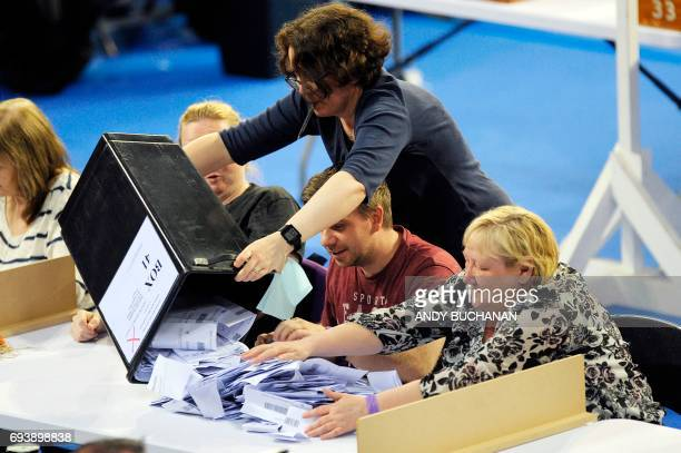 Staff members empty a ballot box at the main Glasgow counting centre in Emirates Arena in Glasgow Scotland on June 8 after the polls closed in...