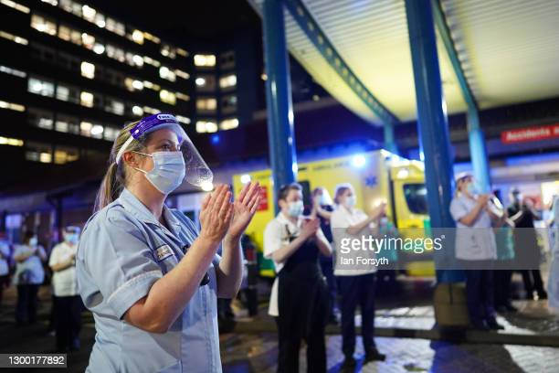 Staff members gather outside the entrance of University Hospital of North Tees to show their respects and applaud Captain Sir Tom Moore on February...