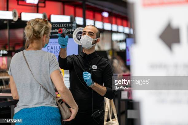 Staff members give hand-sanitizing gel and test customers temperature inside of Sephora store during the first day of activities reopening after...