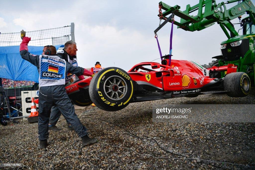 TOPSHOT - Staff members help as a tractor lifts the car of Ferrari's German driver Sebastian Vettel during the German Formula One Grand Prix at the Hockenheim racing circuit on July 22, 2018 in Hockenheim, southern Germany.
