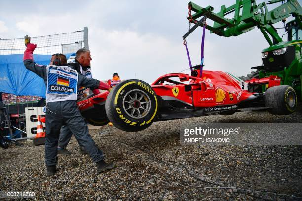 TOPSHOT Staff members help as a tractor lifts the car of Ferrari's German driver Sebastian Vettel during the German Formula One Grand Prix at the...