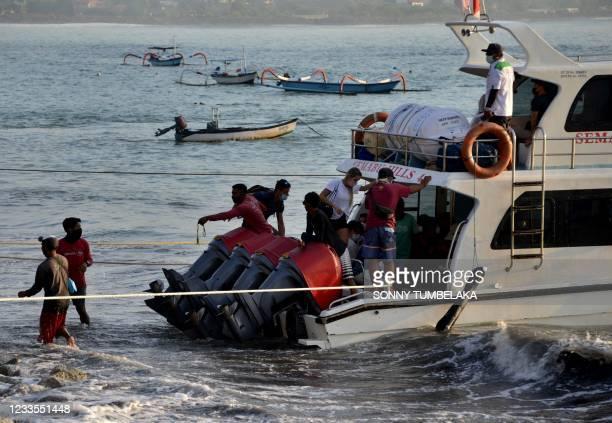 Staff members help load tourists onto a boat near Sanur beach to cross to the nearby island of Nusa Penida, on Indonesia's resort island of Bali...