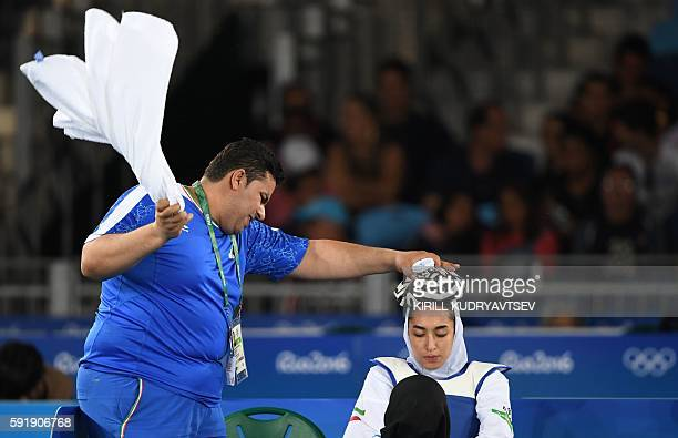 Staff members holds an ice pack on the head of Iran's Kimia Alizadeh Zenoorin during a break as she competes against Sweden's Nikita Glasnovic during...