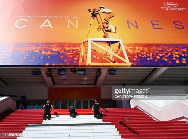 TOPSHOT Staff members install the red carpet outside the festival palace on May 14 2019 ahead of the opening of the 72nd edition of the Cannes Film...