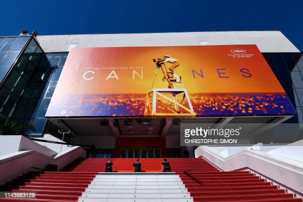 Staff members install the red carpet outside the festival palace on May 14 2019 ahead of the opening of the 72nd edition of the Cannes Film Festival...