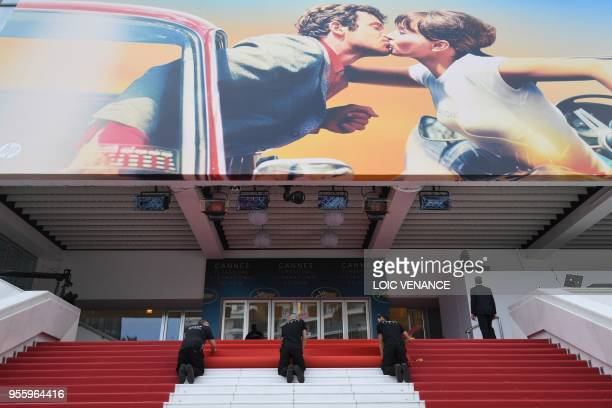 TOPSHOT Staff members install the red carpet outside the festival's palace on May 8 2018 ahead of the opening of the 71st edition of the Cannes Film...