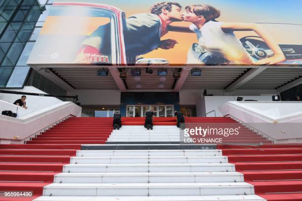 Staff members install the red carpet outside the festival's palace on May 8 2018 ahead of the opening of the 71st edition of the Cannes Film Festival...
