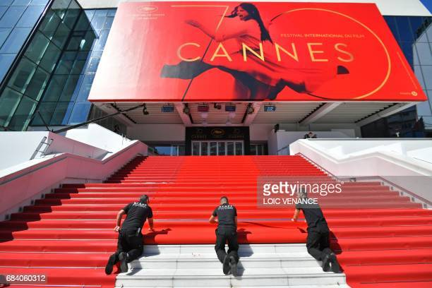 Staff members lay out the red carpet outside the Palais des Festivals in the southeastern French city of Cannes on May 17, 2017 in Cannes, before the...