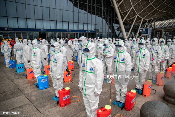 TOPSHOT Staff members line up at attention as they prepare to spray disinfectant at Wuhan Railway Station in Wuhan in China's central Hubei province...