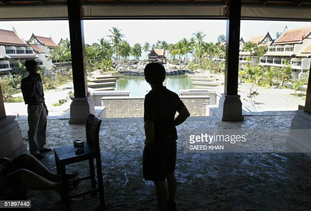 Staff members look at the devastation at the Sofitel hotel where hundreds of guests are still missing along the shoreline of Khao Lak a province...