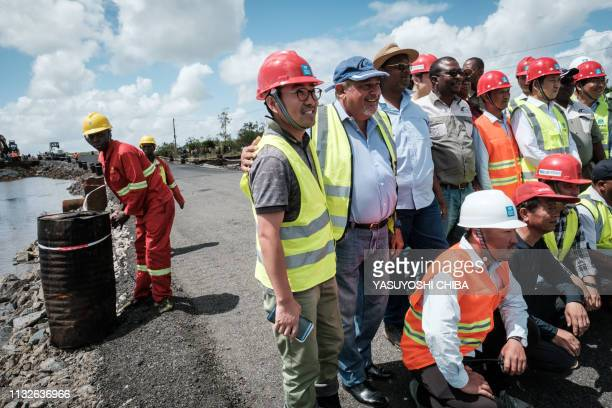 Staff members of China State Construction pose for a photo before the opening of the N6 road reconstructed in three days after the original road was...