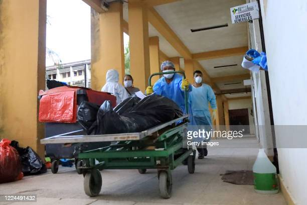 Staff members of Felipe Arriola Iglesias Hospital wearing PPE push a trolley with a corpse wrapped in a plastic bag towards the mortuary refrigerator...
