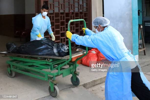 Staff members of Felipe Arriola Iglesias Hospital wearing PPE take a corpse wrapped in a plastic bag towards the mortuary refrigerator on May 09,...