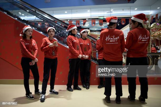 Staff members of Hamleys wait for customers on the opening day of a new Hamleys store the iconic British toy retailer now Chineseowned in Beijing on...