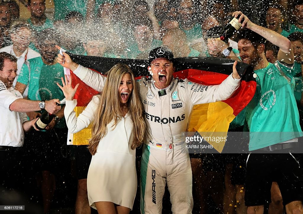 Staff members of Mercedes AMG Petronas F1 Team spray German driver Nico Rosberg (C-R) and his wife Vivian Sibold with champagne as they celebrate at the end of the Abu Dhabi Formula One Grand Prix at the Yas Marina circuit on November 27, 2016. Nico Rosberg won his maiden Formula One world title by securing second place behind his Mercedes arch-rival Lewis Hamilton in the Abu Dhabi Grand Prix. / AFP / KARIM