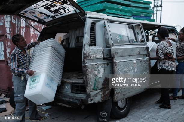 Staff members of the Independent National Electoral Commission unload ballot boxes from a van outside their local office in Port Harcourt Southern...