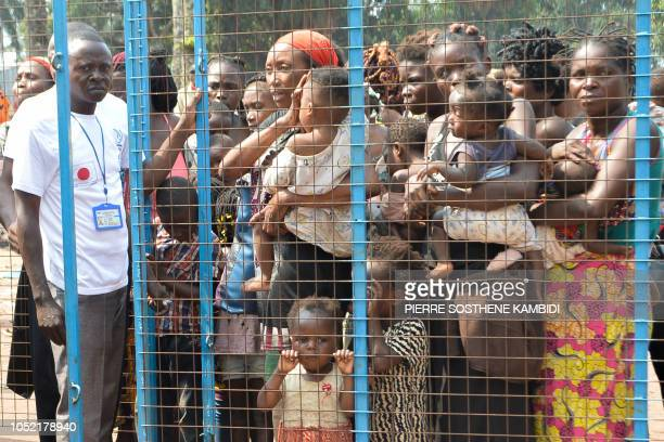 Staff members of the International Organisation for Migration assist Congolese migrants who were living in Angola to cross the border near the...