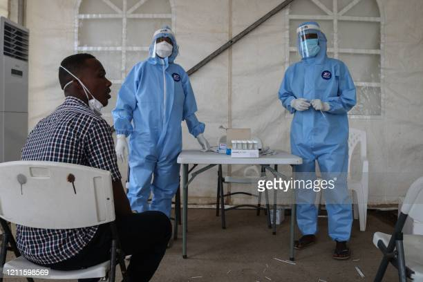 Staff members of the Ministry of Health prepare to take samples for testing for the COVID-19 coronavirus at the testing unit at the Bouffard hospital...