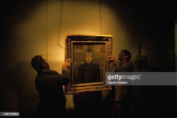 Staff members of the museum hang Toulouse Lautrec's famous painting 'Filles de Montmartre' in the exhibition hall of the Museum of Contemporary Art...