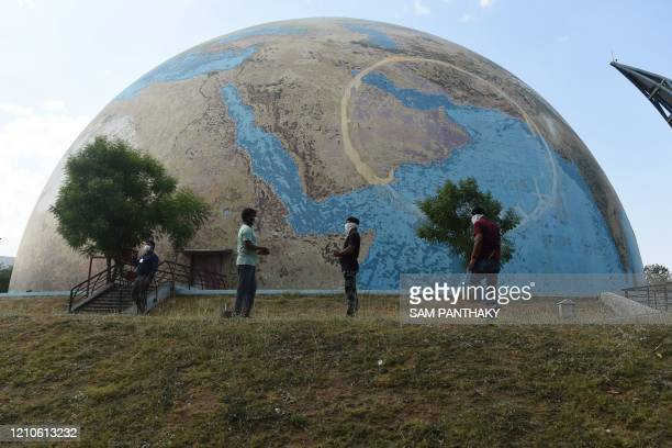 Staff members of the the Gujarat Science City wearing facemasks stand in front of a planet earth model on the eve of World Earth Day at Gujarat...