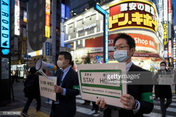 Staff members of the Tokyo metropolitan government wearing face masks hold signs as they call people to stay home in the Kabukicho entertainment area...