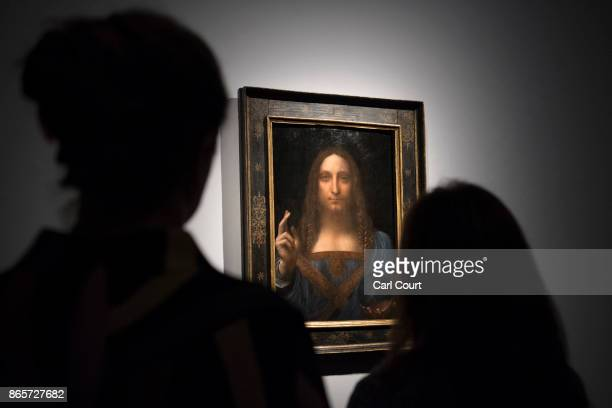 Staff members pose next to a painting by Leonardo da Vinci entitled 'Salvator Mundi' before it is auctioned in New York on November 15 at Christies...