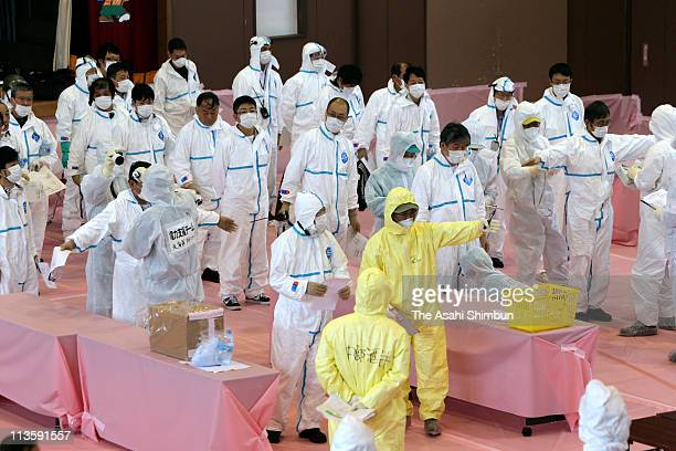 Staff members receive the radioactive check after retuning from 5km point from the troubled Fukushima Daiichi Nuclear Power Plant exclusion zone at...
