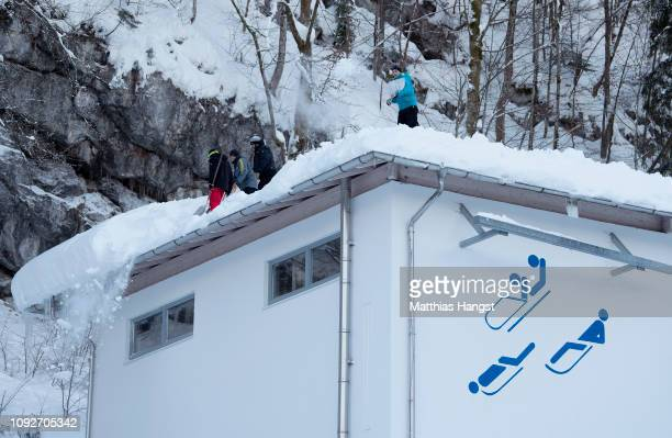 Staff members remove snow from the roof of the start house building after the cancellation of the 4. BMW IBSF Skeleton Worldcup at Deutsche Post...